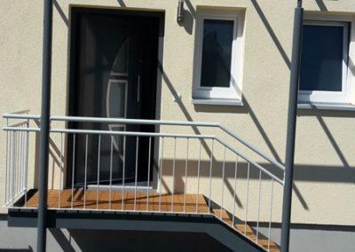 Eingangspodest mit Holzbelag darüber eine Überdachung integriert